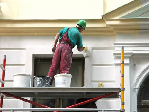 exterior painting of a house from yellow to white
