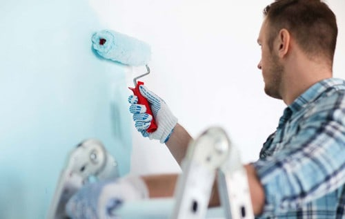 upclose photo of a man painting a white wall blue