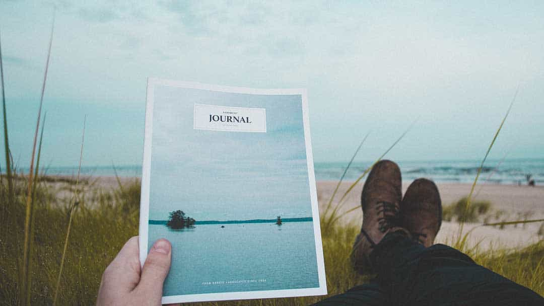 person holding journal at the beach relaxed