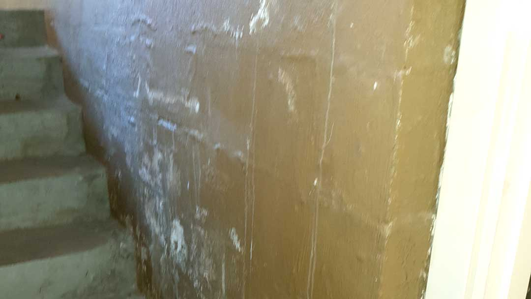 damp bubbled paint on concrete wall