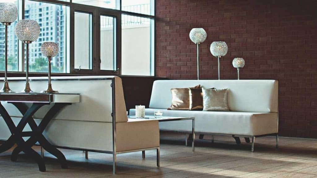 cream leather couches with brown brick feature wall