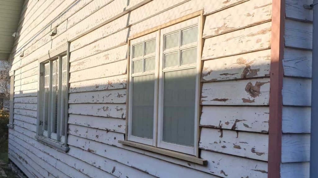 old weather board home with peeling paint