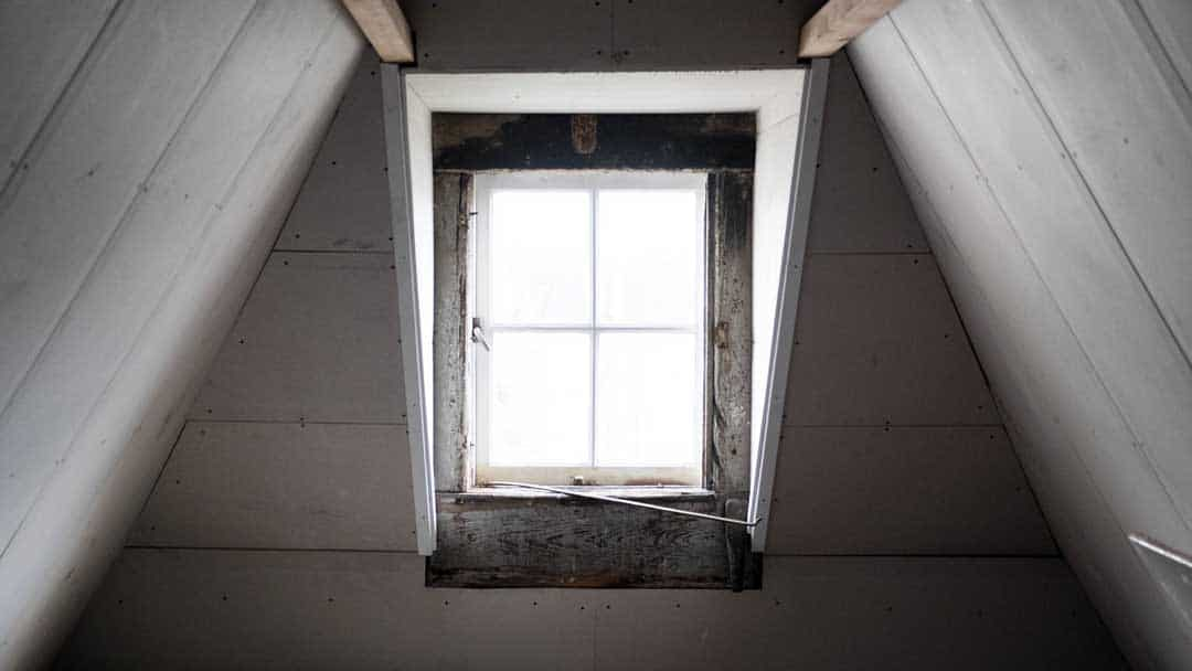 photo of attic window looking out with white painted timber