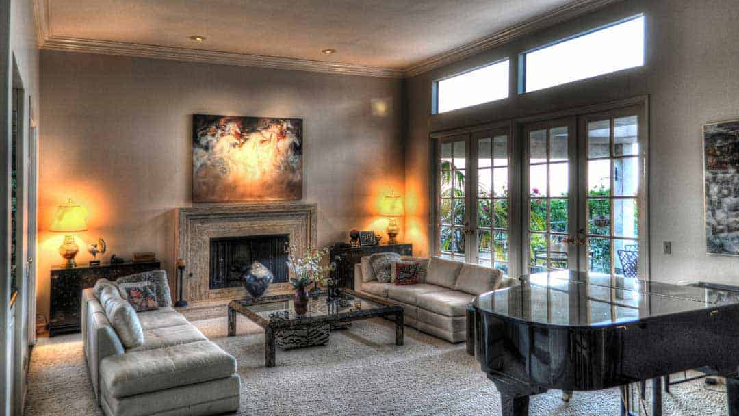 beautiful living room with fire place looking out windows to a garden