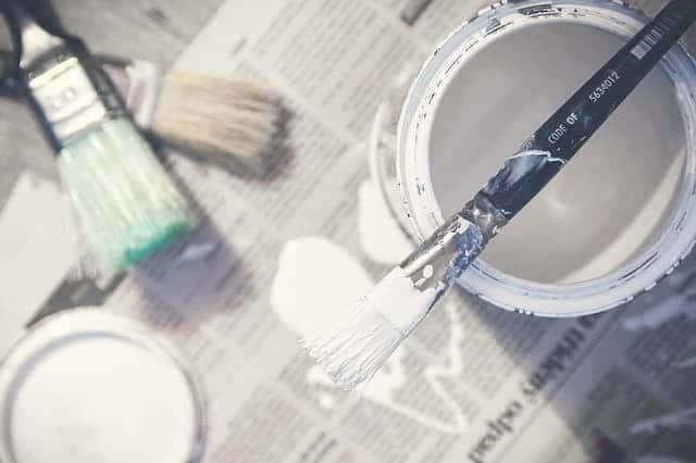 newspaper with white paint can and brush on top