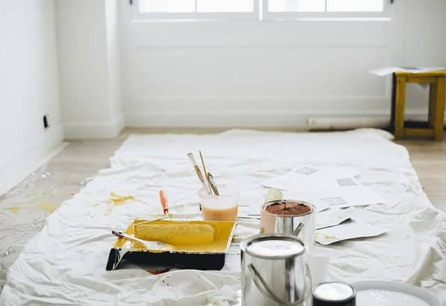 white painters drop cloth with paint can and paint brushes