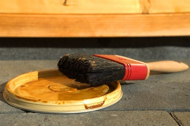 close up of a paint brush leaning on a paint lid