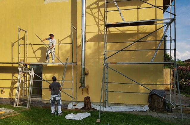 Exterior building wall with two men painting