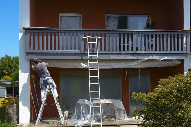 front of home with man painting double story deck