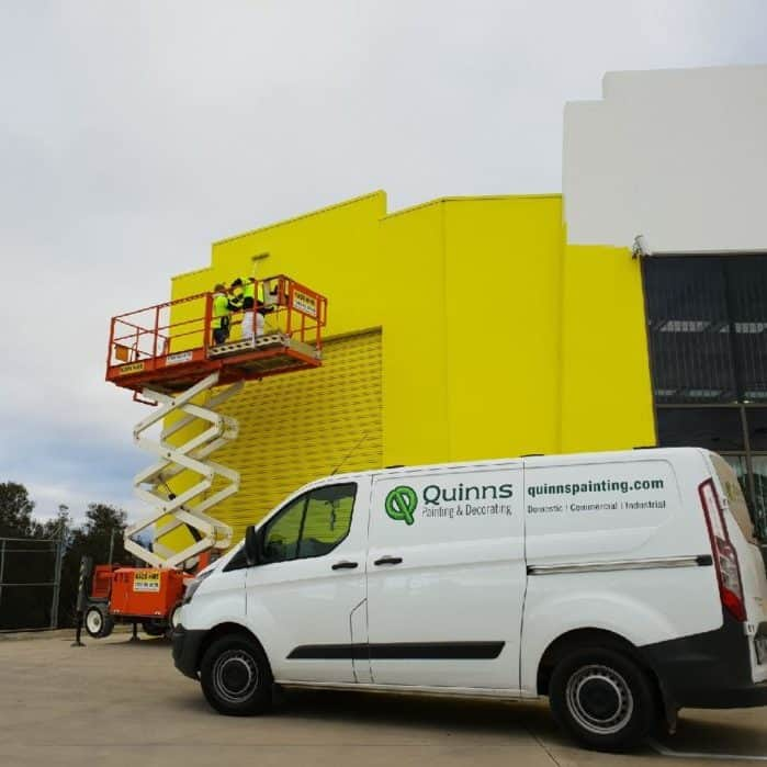 quinns painting & decorating van out the front of an industrial painting job, external painting, yellow factory and roller door