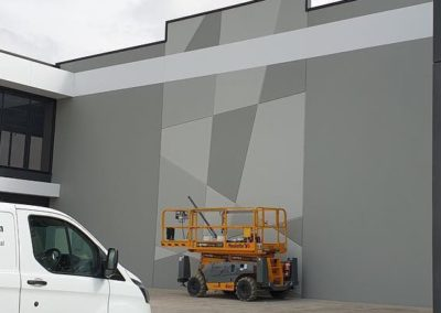 external painting of a factory, the wall has an asymmetrical and angular feature wall painted by quinns painting