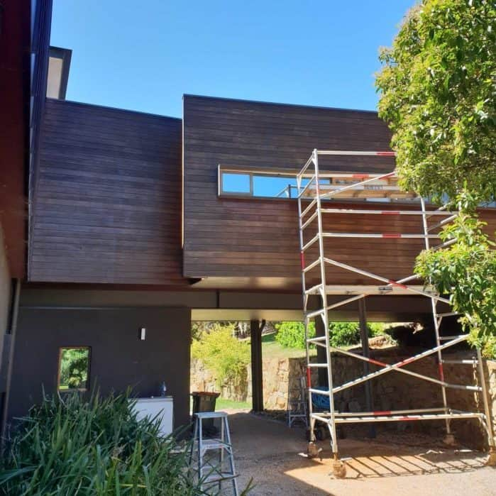 staining of house exterior wood on a modern home, using scaffolding because its high up