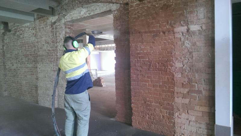 Cleaning brick wall by sandblasting