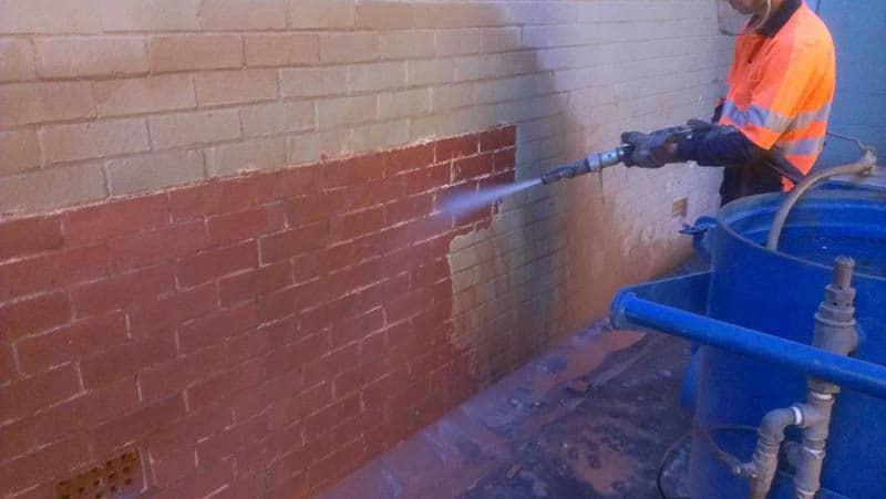 Sandblasting paint off a brick wall