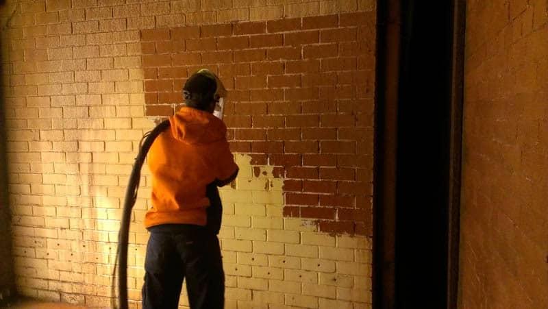 Sandblasting paint off cream bricks